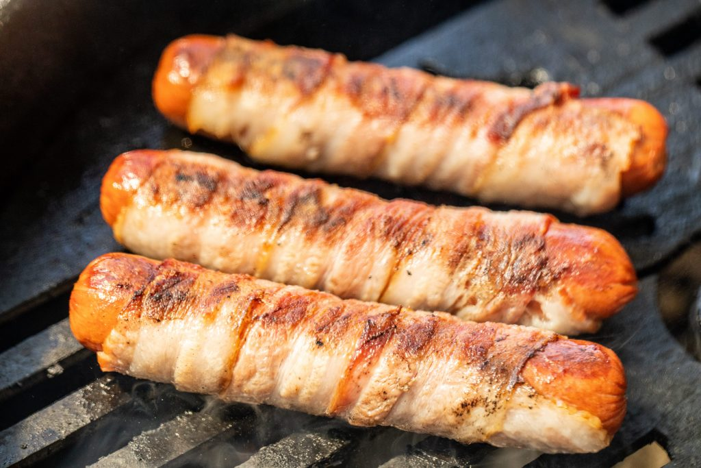 Bacon wrapped Sonoran Hot Dogs on a grill.