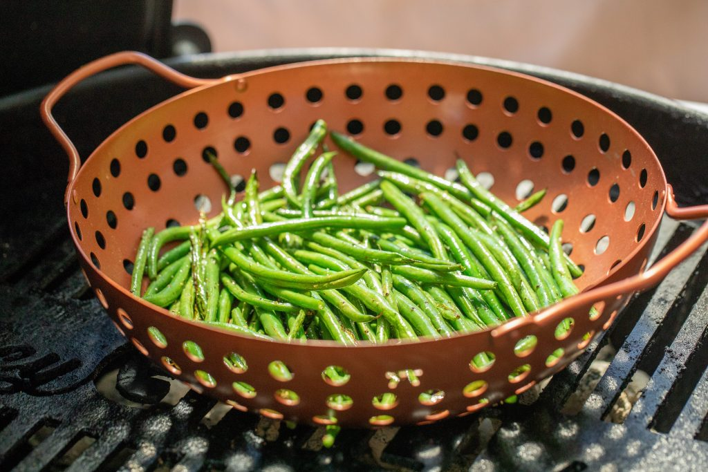 Fresh green beans in a vegetable grilling basket on a charcoal grill.