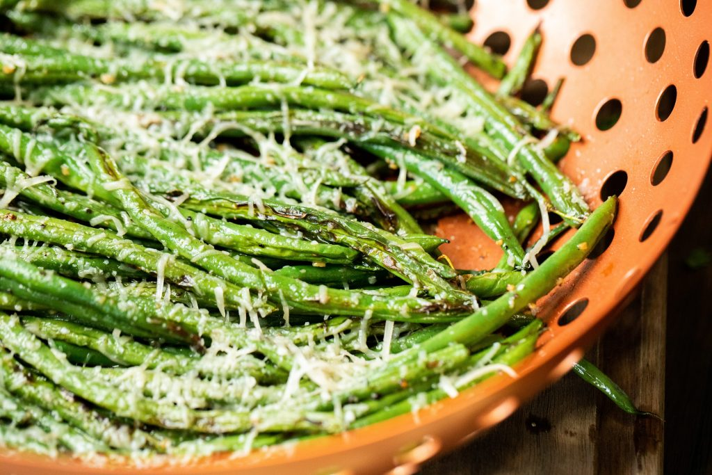 Close up of garlic parmesan grilled green beans in a grilling basket.