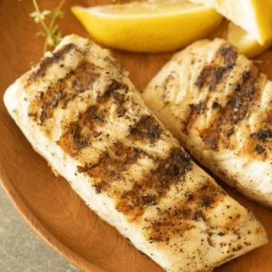 grilled halibut on a wooden plate
