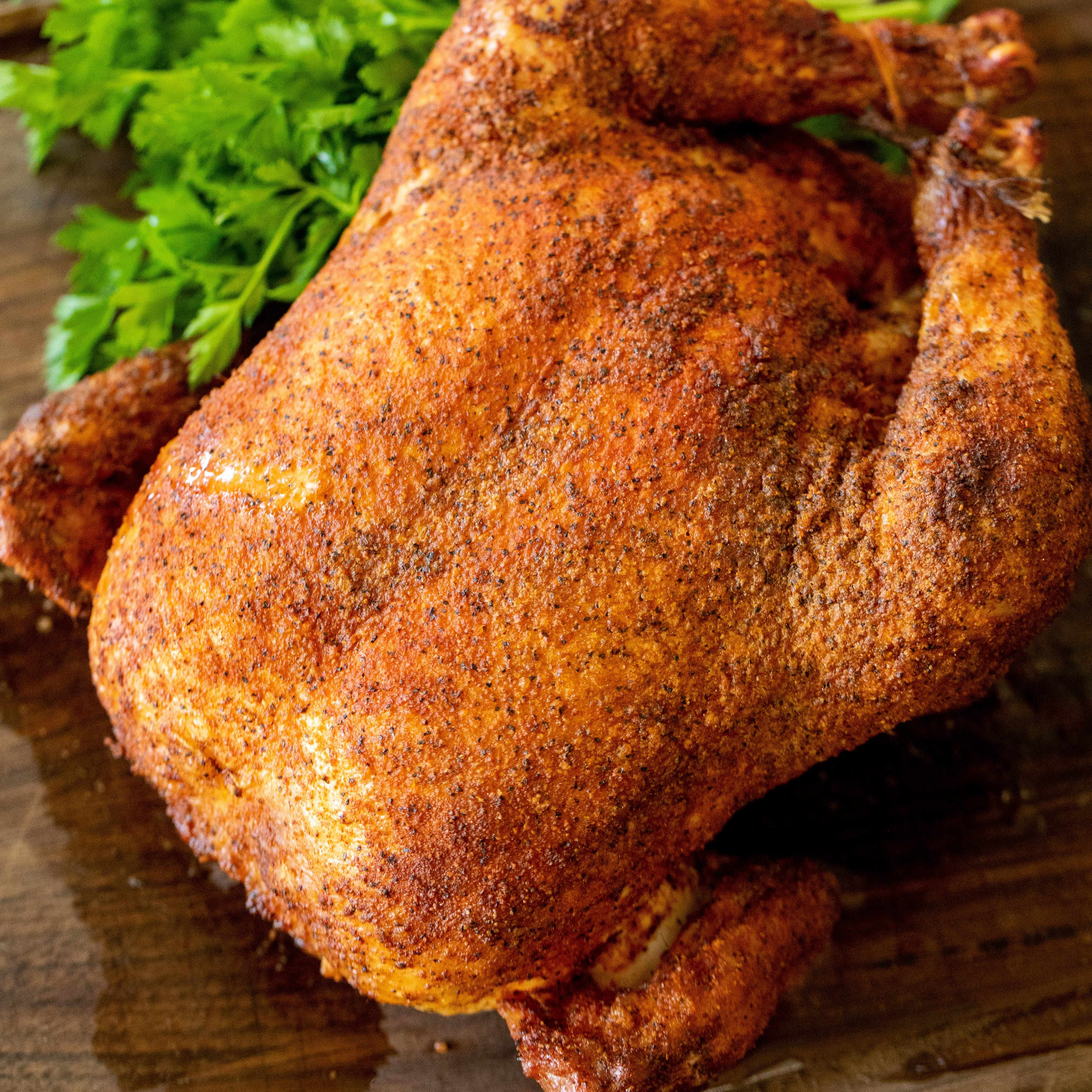 Smoked whole chicken on a wooden cutting board next to fresh herbs.