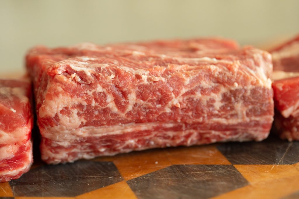 raw beef short ribs on a wooden cutting board.