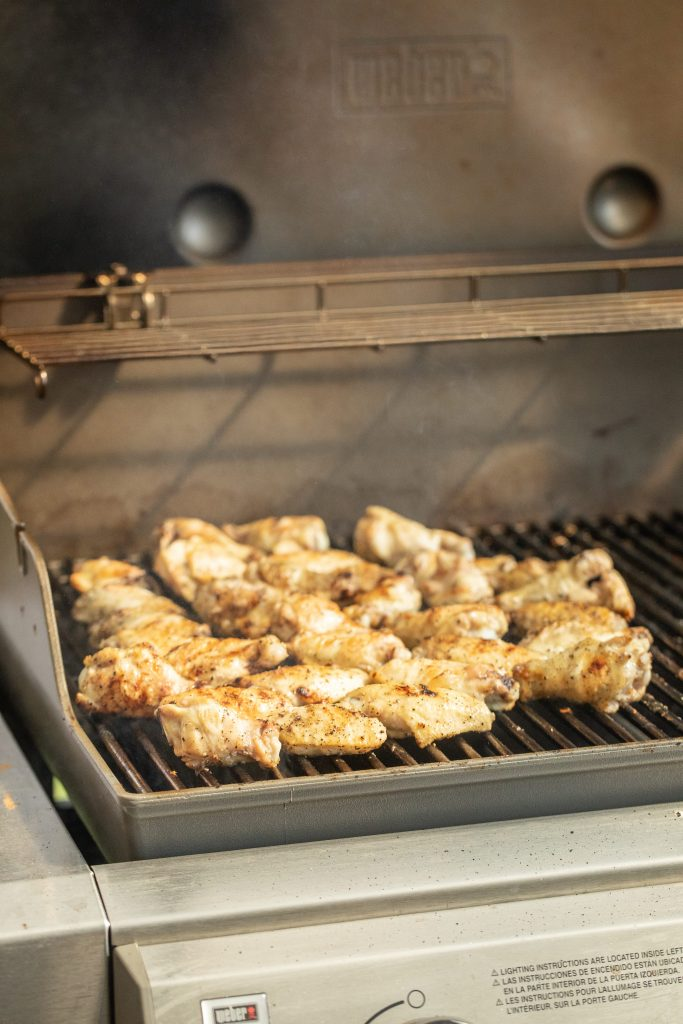 chicken wings cooking on an open grill.