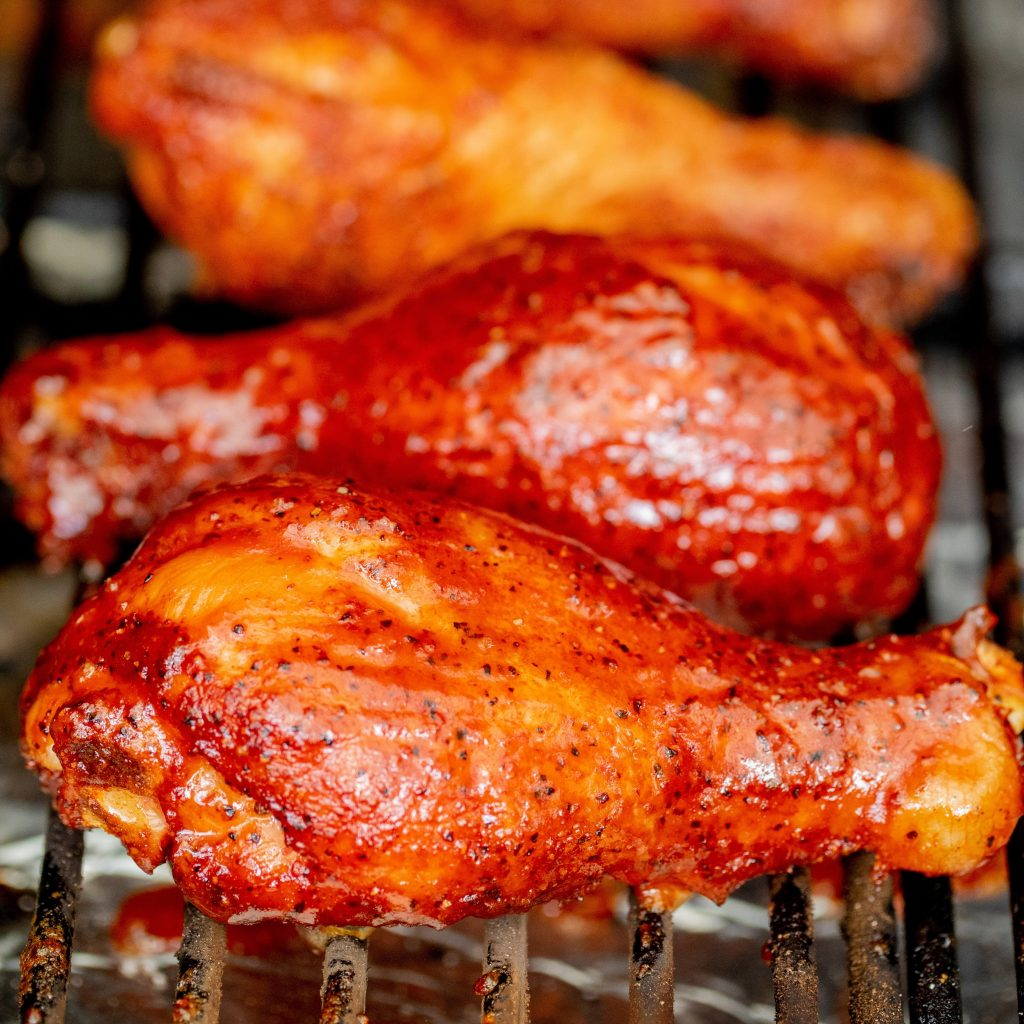 Four smoked chicken legs lined up on the grill grates of a pellet smoker.