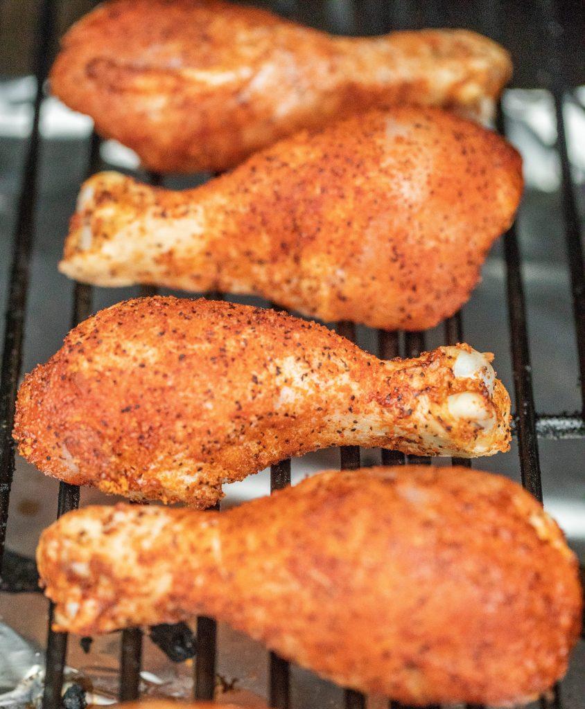 seasoned chicken legs on grill grates.