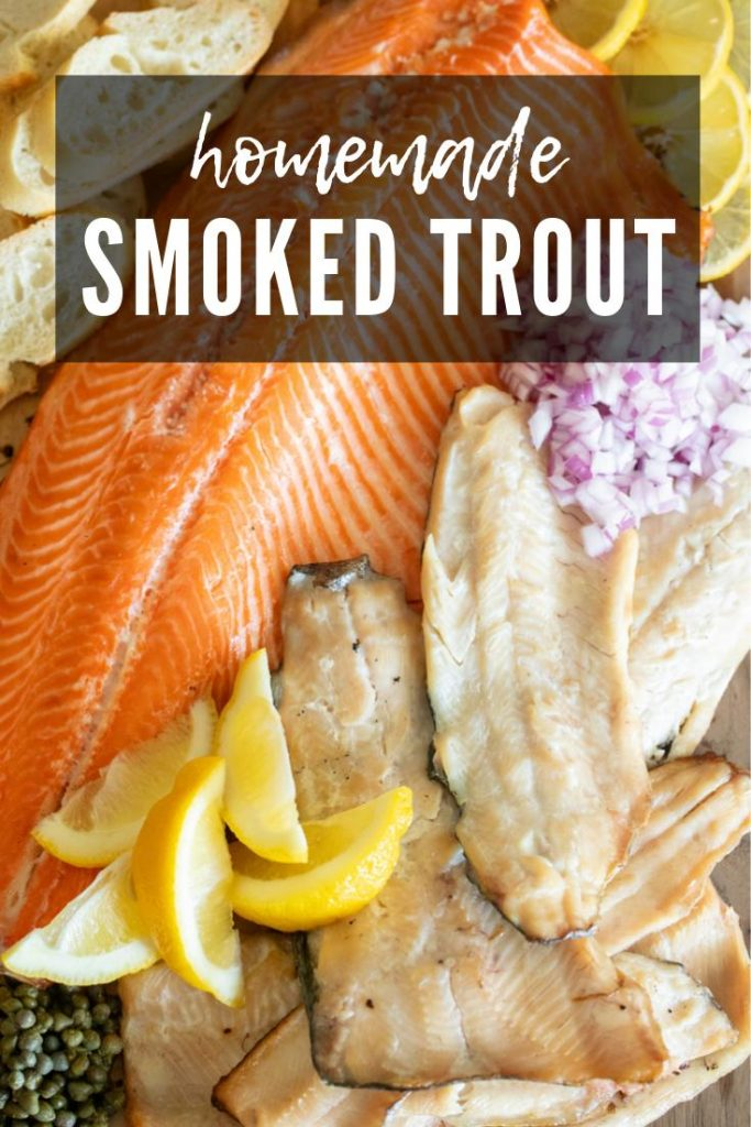 smoked trout filets with lemon wedges, red onions, and capers on a wood board.