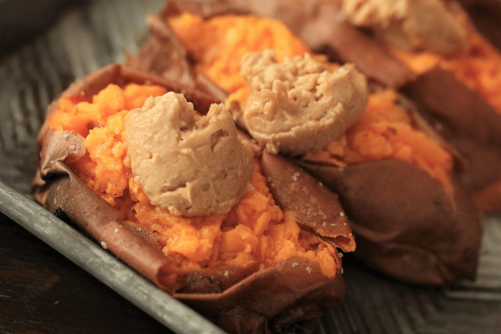 two smoked sweet potatoes each with a spoonful of maple cinnamon butter.