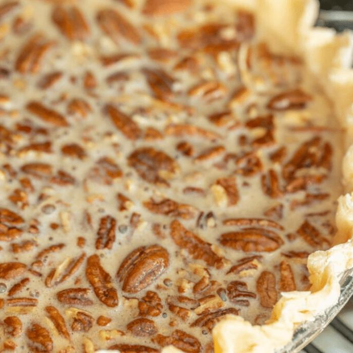 Close up of smoked pecan pie in a metal pie tin.