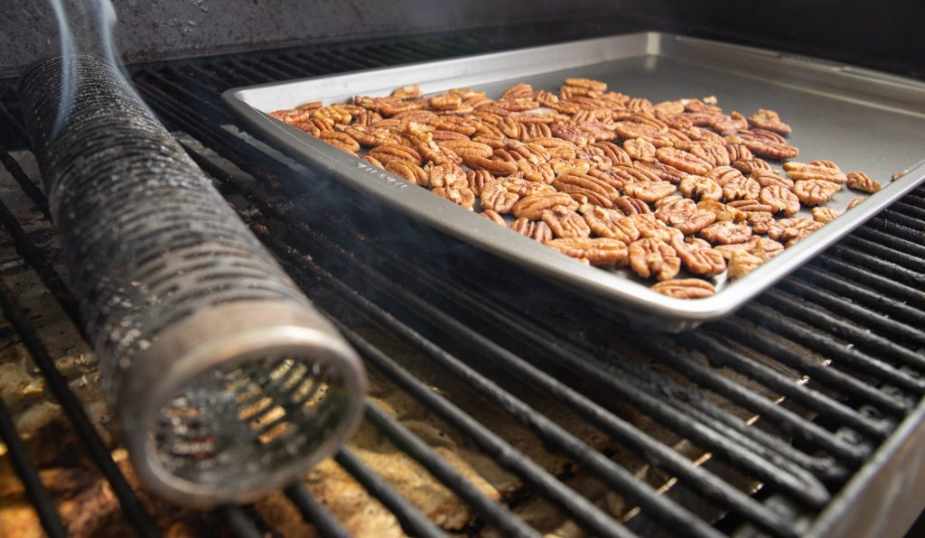 baking tray of pecans on the grill grates in a smoker next to a smoke tube.