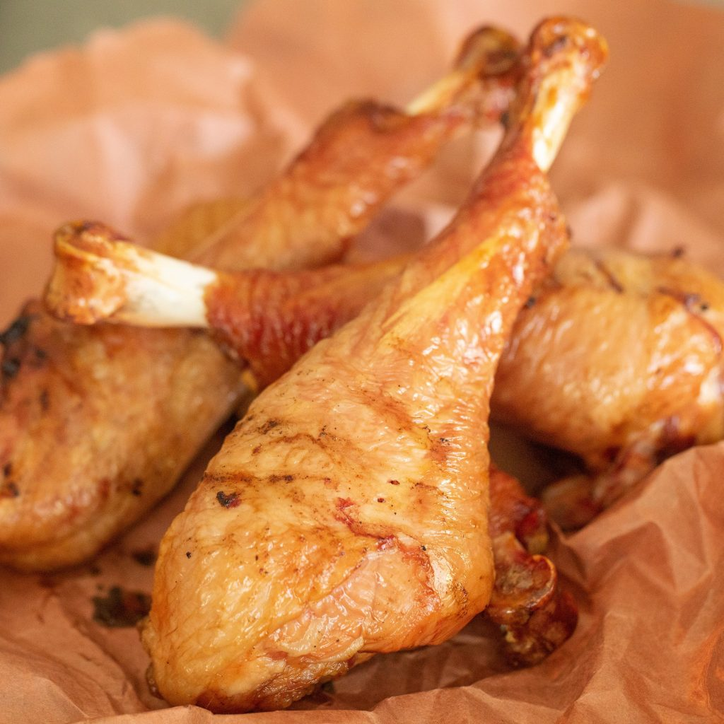 Smoked turkey legs piled on top of peach butcher paper.