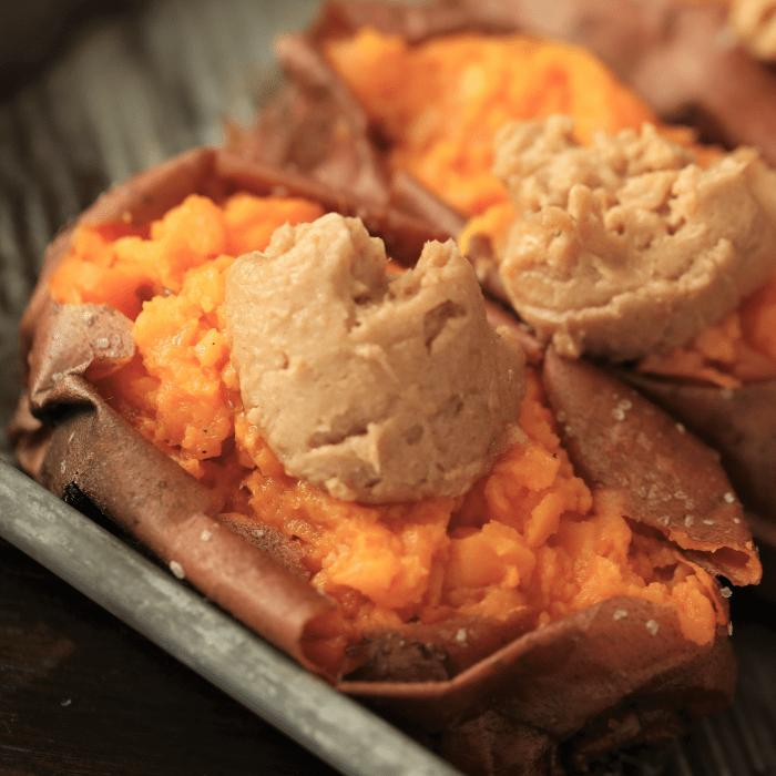 Two smoked sweet potatoes topped with maple cinnamon butter in a metal baking dish.
