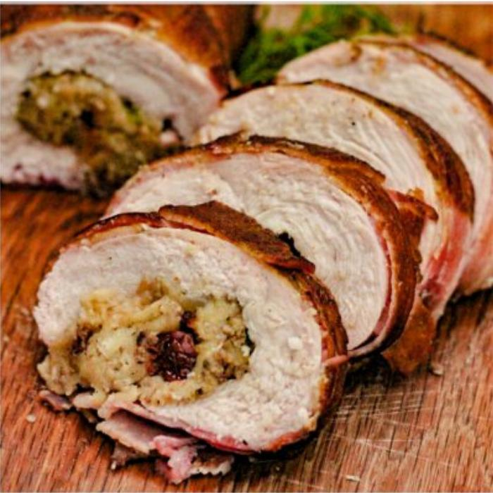 Sliced turkey breast roulade on a wooden cutting board.