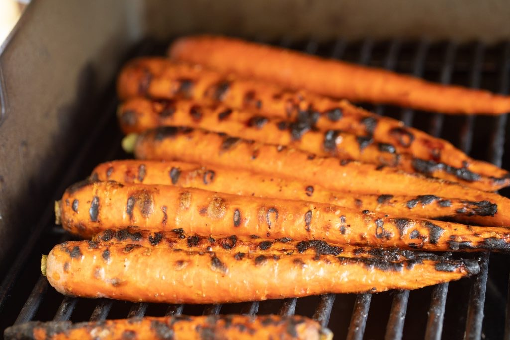 seasoned carrots with blackened grill marks on a gas grill.
