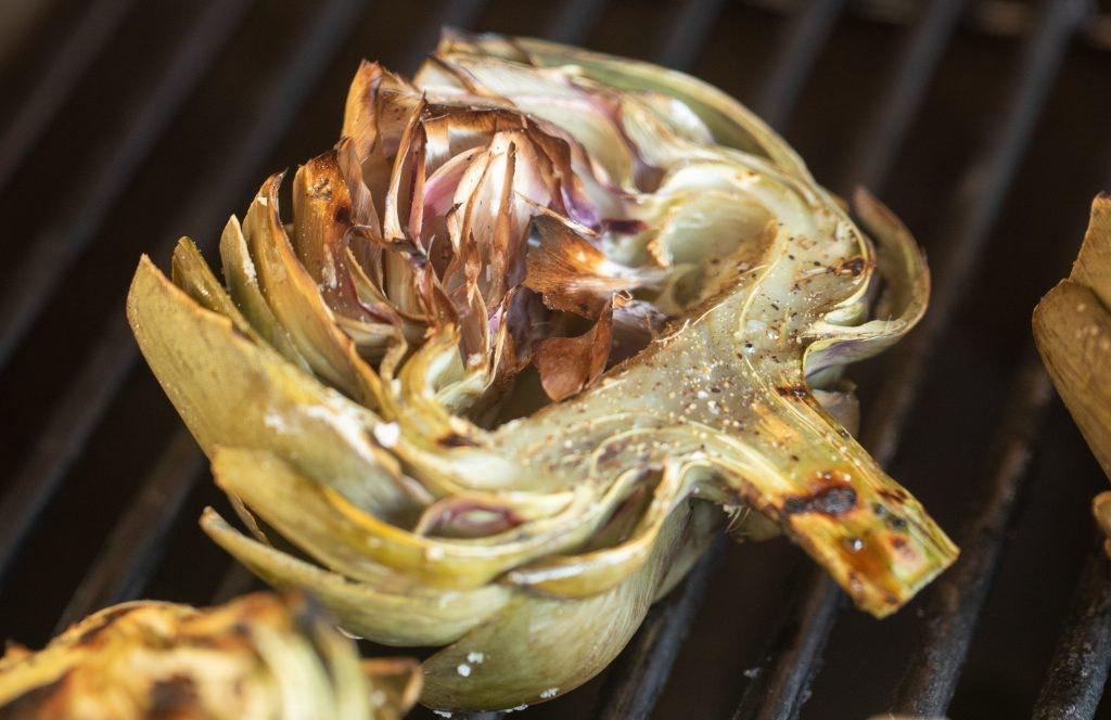 Seasoned artichoke halves on the grill.