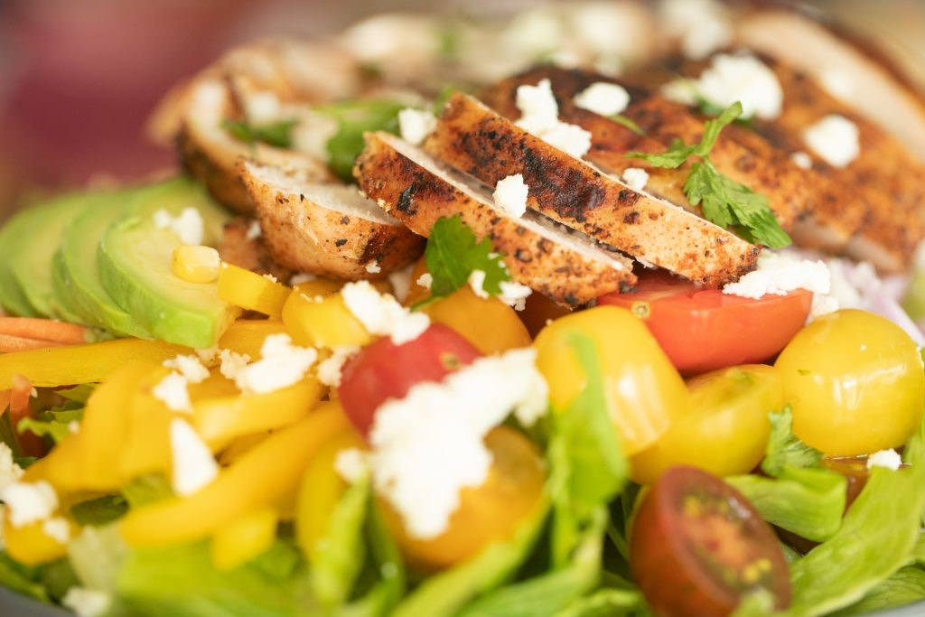close-up image of grilled chicken on top of a bed of lettuce and vegetables.