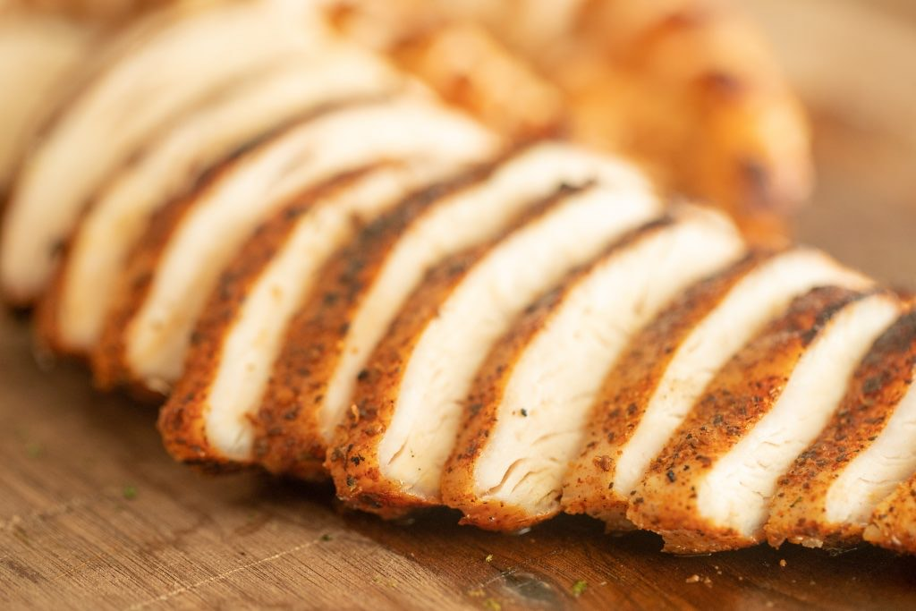 sliced grilled chicken for southwest grilled chicken salad on a wooden cutting board.