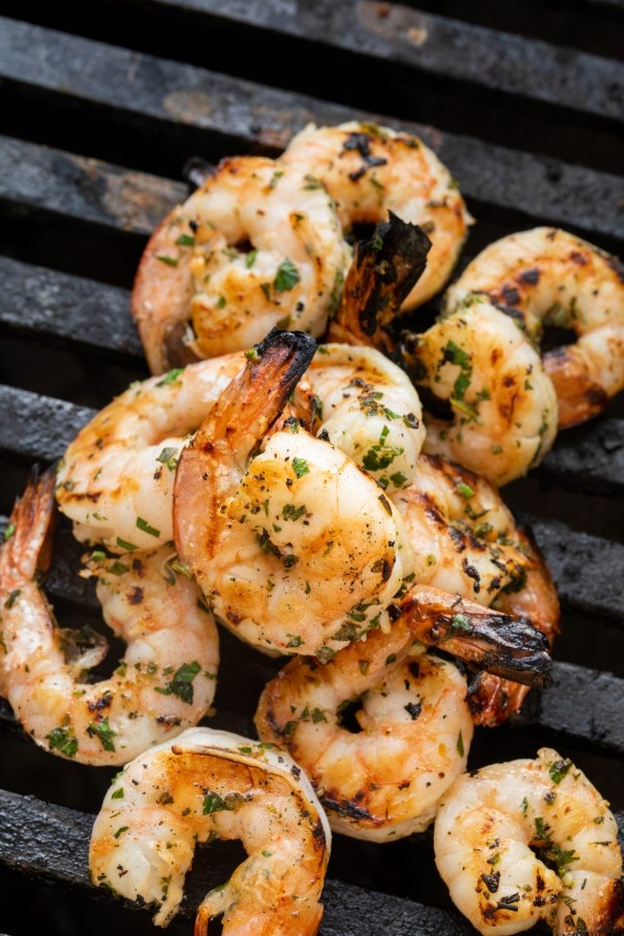 marinated shrimp on the grill grates of a grill.