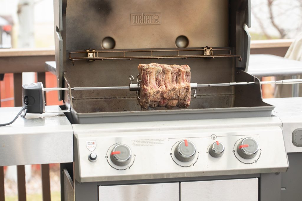 seasoned prime rib on a rotisserie attachment on a gas grill.