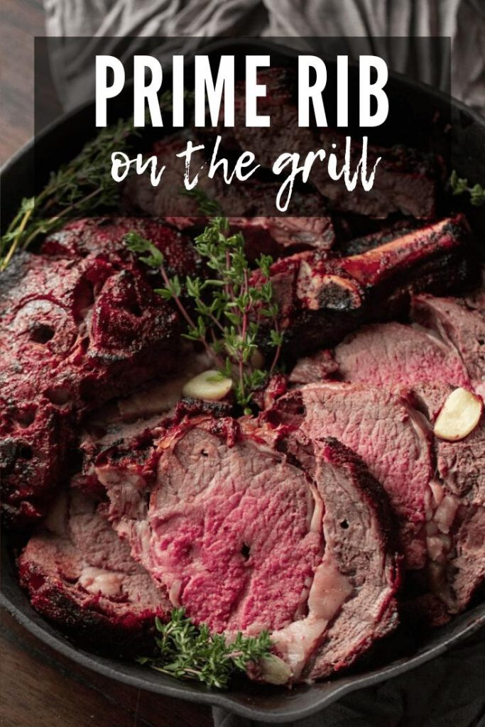 sliced prime rib cooked on the grill in a cast iron skillet with fresh herbs and garlic cloves.