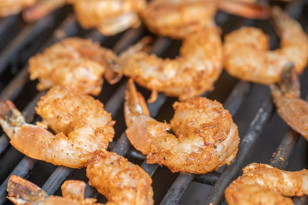 Seasoned shrimp on the grill grates of a charcoal grill.