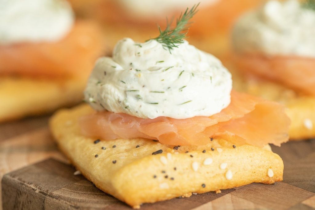 smoked salmon appetizer on a wooden cutting board.