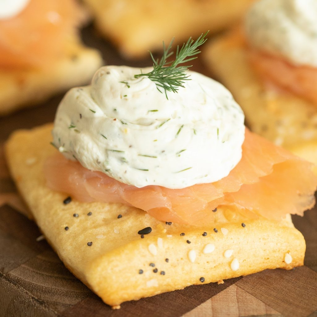 Crescent dough crostini topped with smoked salmon and lemon dill cream cheese on a wooden cutting board.