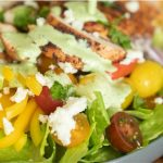 Close up image of grilled chicken salad drizzled with jalapeno lime ranch.