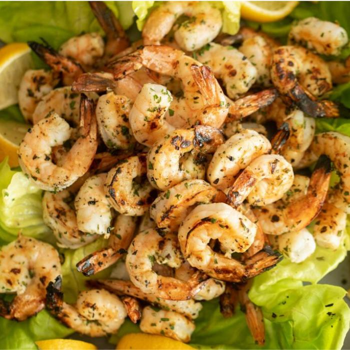Marinated and grilled shrimp piled on a bed of lettuce and sliced lemons.