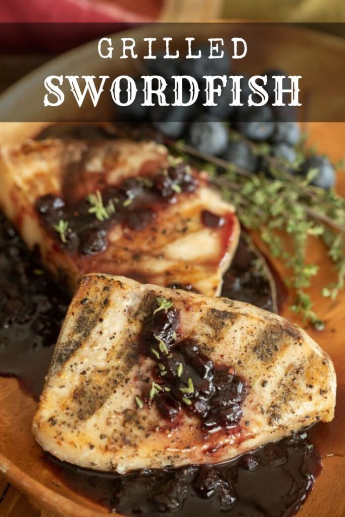 two grilled swordfish fillets topped with a blueberry balsamic reduction in a wooden bowl.