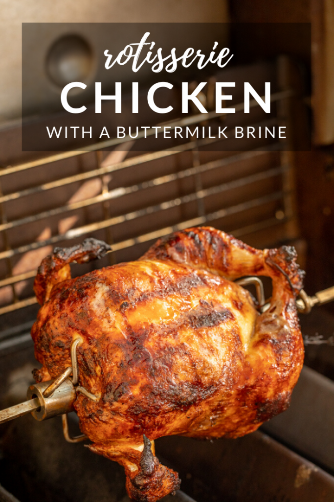 whole fryer chicken on a rotisserie spit in a grill. Text overlay reads, Rotisserie Chicken with a buttermilk brine.