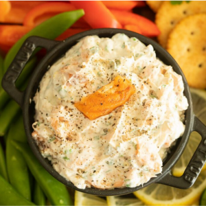 Overhead shot of smoked trout dip in a black bowl surrounded by crackers and sliced veggies.