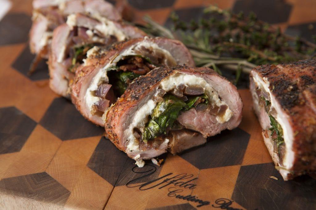 Sliced bacon wrapped stuffed pork tenderloin on a wooden board.