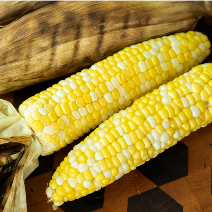 Two grilled and husked ears of corn on a wooden cutting board.