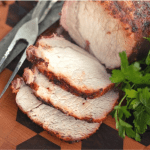 Grilled pork loin sliced into three slices next to a metal fork and knife and fresh herbs on a wooden cutting board.