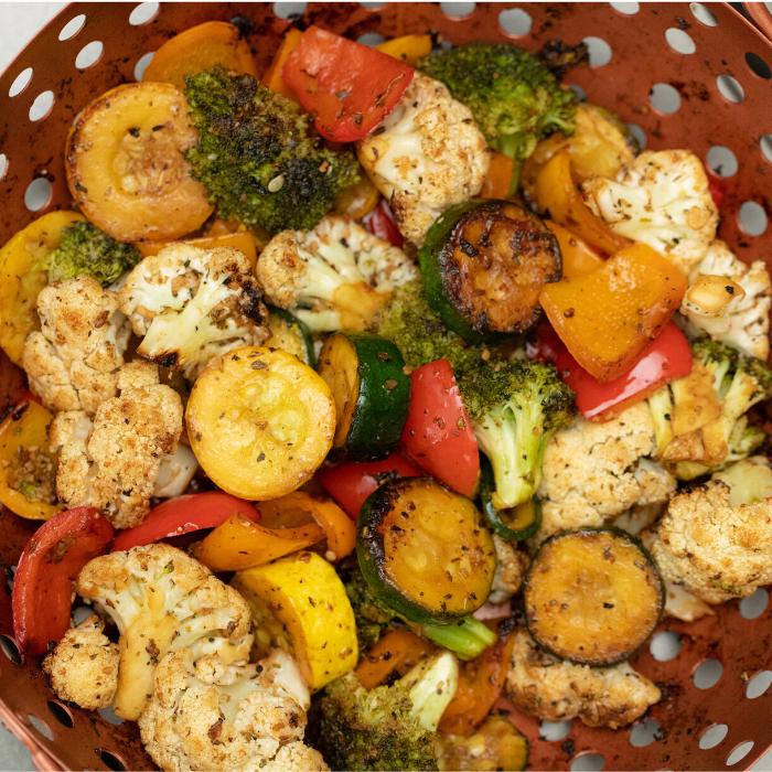 Grilled vegetables in a copper vegetable grill basket.