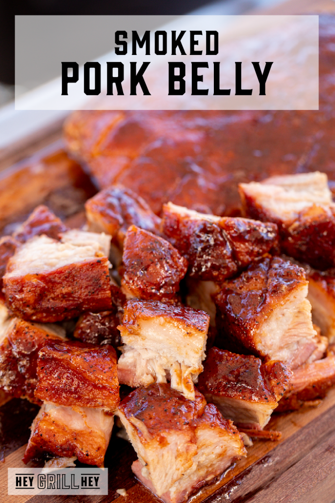 Pile of cubed pork belly on a wooden cutting board with text overlay - Smoked Pork Belly.