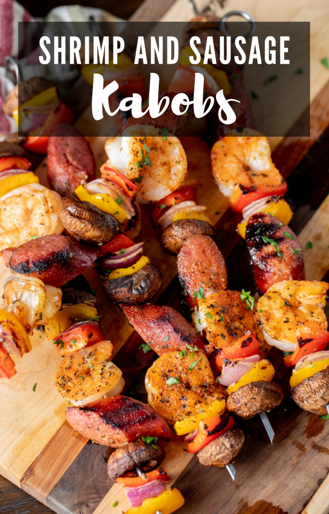 grilled shrimp and sausage kabobs stacked on a wooden cutting board.
