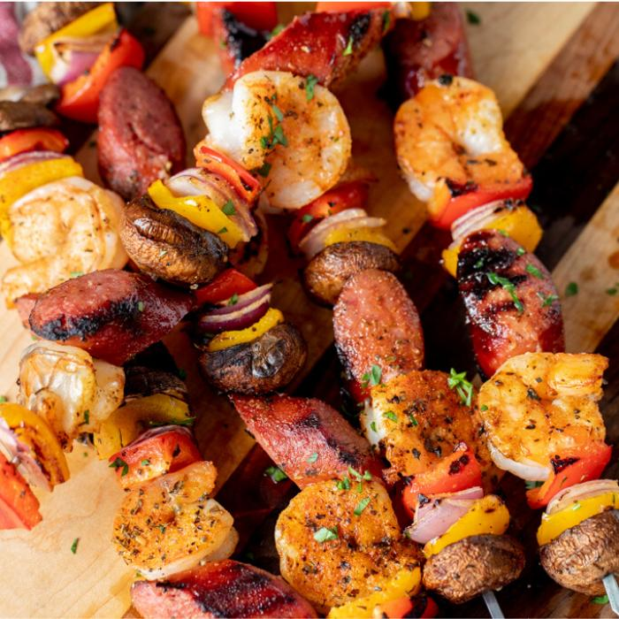 Shrimp and sausage kabobs stacked on a wooden cutting board.