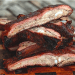 Sliced smoked spare ribs stacked on a wooden cutting board.