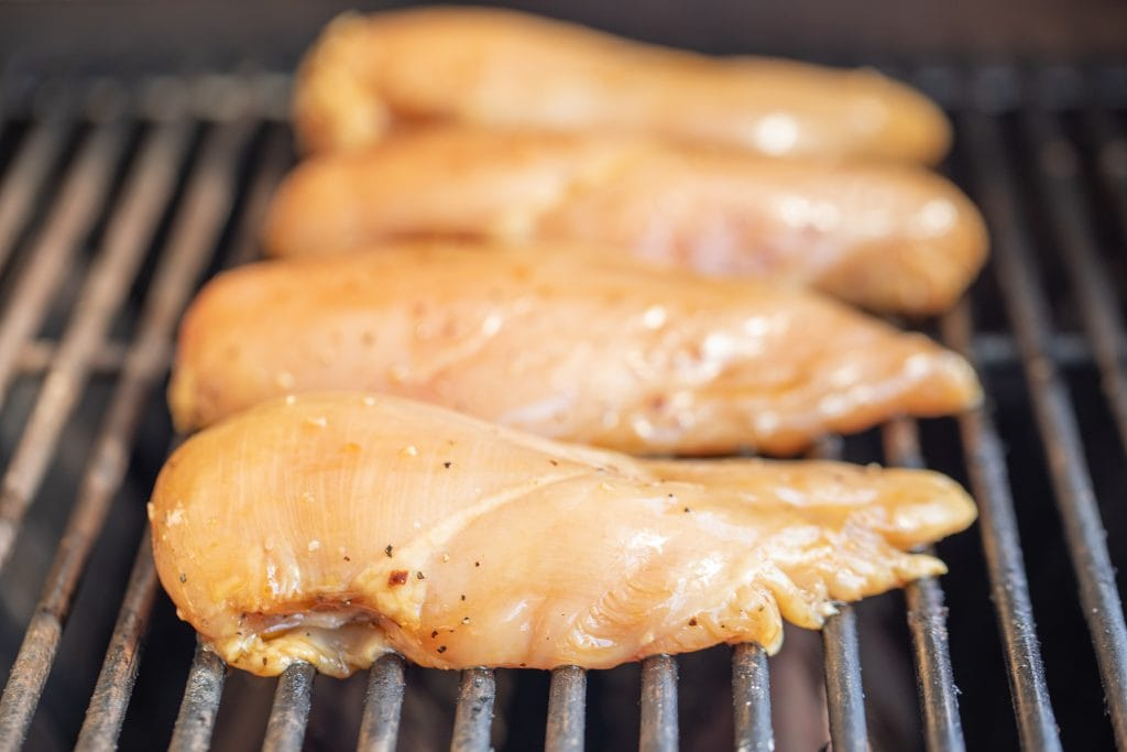 Four marinated chicken breast on the grill grates of a gas grill.