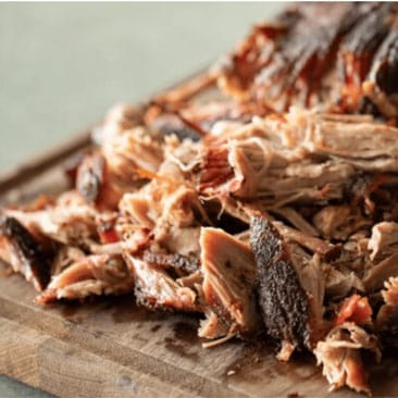 Carolina pulled pork shredded and stacked on a wooden cutting board.
