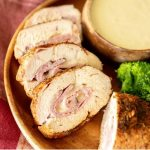 Sliced cross section of grilled chicken cordon bleu next to a bowl of dipping sauce and broccoli florets.