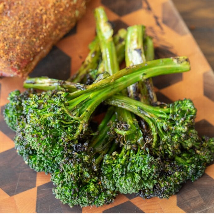 Stalks of Grilled broccolini stacked on a wooden cutting board.