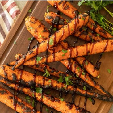 Grilled carrots drizzled with a balsamic glaze stacked on a wooden cutting board.