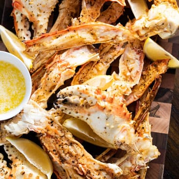 Grilled crab legs next to a small bowl of melted butter stacked on a wooden cutting board.