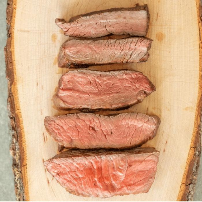 Five sliced steaks showing internal doneness from well done to rare on piece of wood.