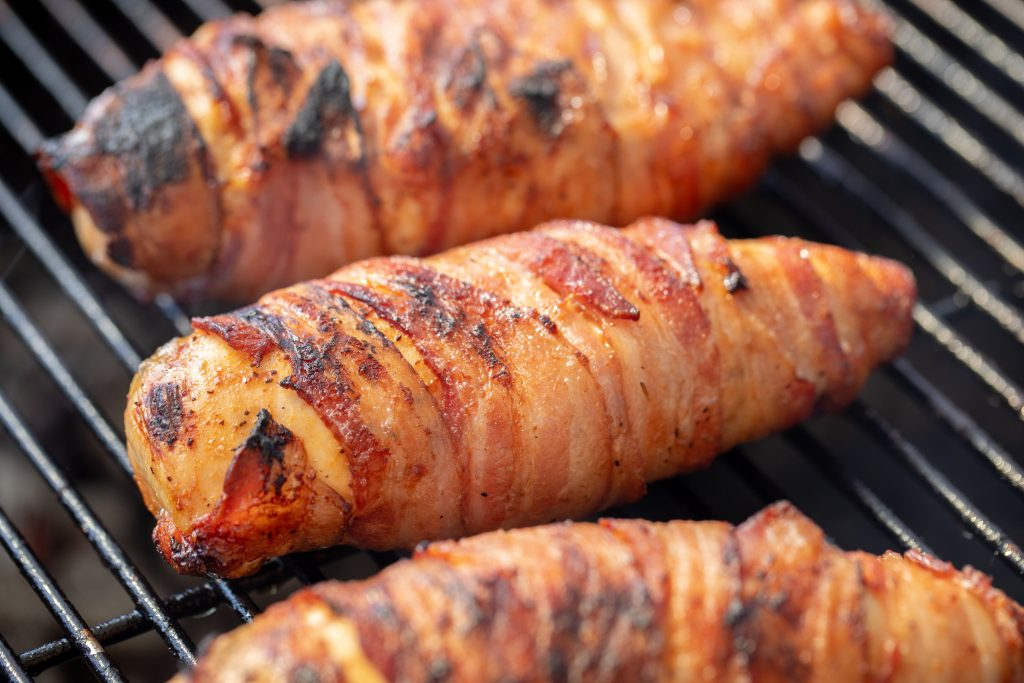 Three bacon wrapped chicken breasts on grill grates