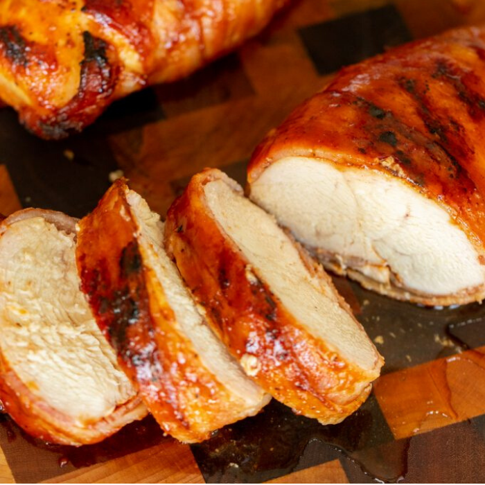 Sliced medallions of a bacon wrapped chicken breast on a wooden cutting board.