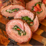 Cross section view of stuffed flank steak slices arranged on a wooden cutting board.