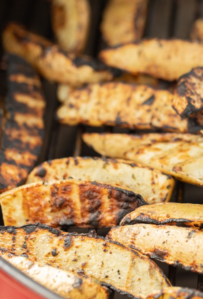 Close- up of grilled potato wedges on the grill grates of a charcoal grill.